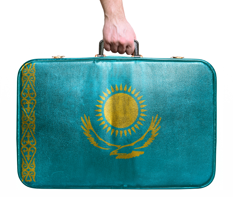 Tourist hand holding vintage leather travel bag with flag of Kaz